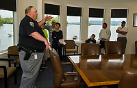 Captain Tim Dunleavy gives visitors a tour of the conference room in the NH Dept of Safety Marine Patrol headquarters during their open house on Saturday morning.  (Karen Bobotas/for the Laconia Daily Sun)