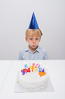 Boy blowing candles on birthday cake at table in house