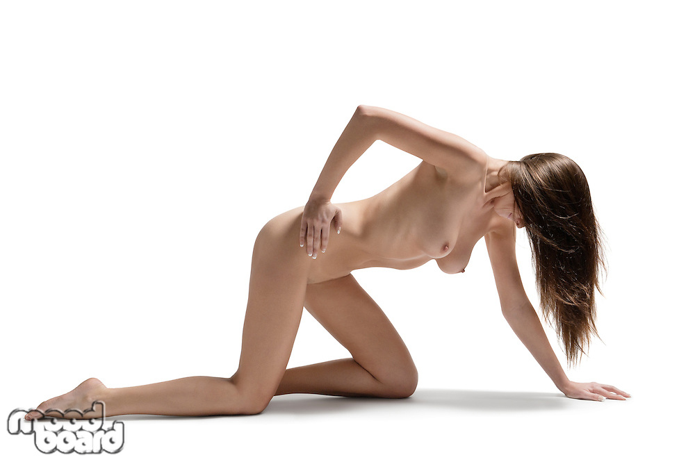 Young woman with hands on hips crawling on hands and knees naked over white background