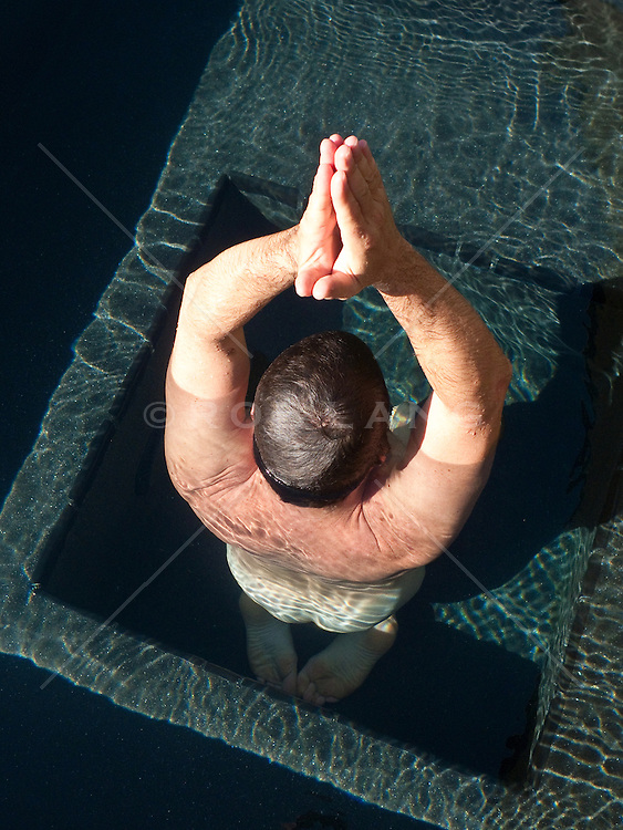 arial view of a man in a pool of water doing naked meditation