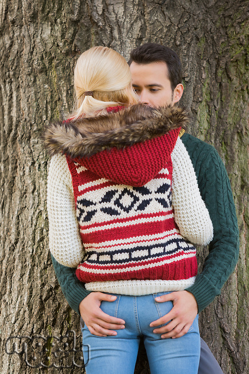 Passionate couple against tree trunk