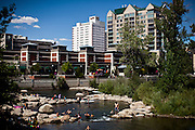 Locals cool off in the Truckee River as it flows through Reno's redeveloped River Walk area in downtown Reno, Nevada, July 6, 2012.