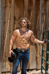 hot muscular cowboy without a shirt by a rustic barn