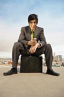 Businessman Sitting on Briefcase
