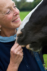 Close up of smiling mature woman pinching a horse nose