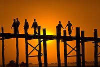 People crossing U Bein Bridge at sunset (longest teak wood bridge in the world), Amarapura, Burma (Myanmar