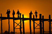 People crossing U Bein Bridge at sunset (longest teak wood bridge in the world), Amarapura, Burma (Myanmar