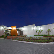 Manenberg Housing Office with metal panels at night, Cape Town, South Africa. City of Cape Town housing and revenue office. 4 Star Green Star SA - Office Design v1 certified. City of Cape Town architecture department.