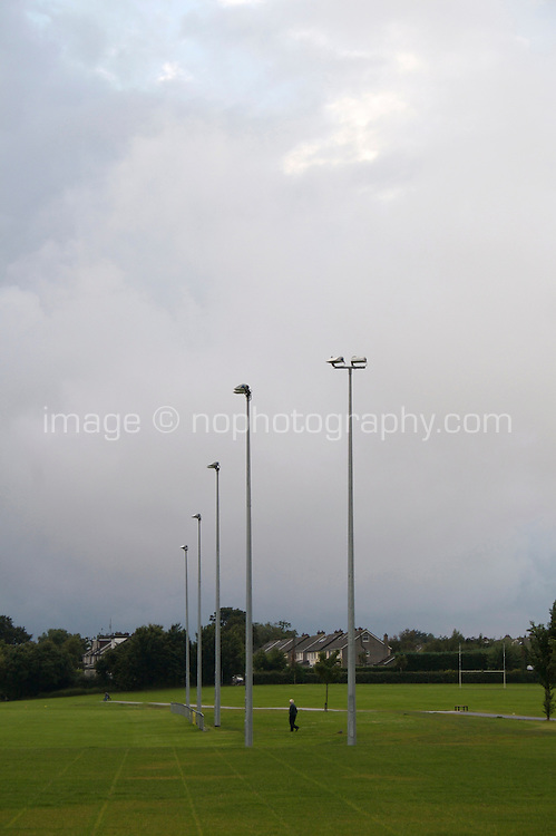 Man walking across football playing field in suburban Dublin Ireland after rainfall