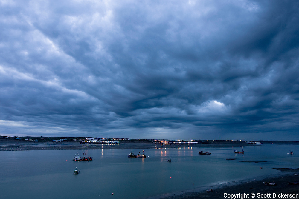 Commercial salmon fishing boats rest at anchor in the Naknek River under a dark cloudy sky, Bristol Bay, Alaska.
