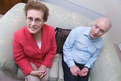 Older couple sitting on a sofa at home smiling,