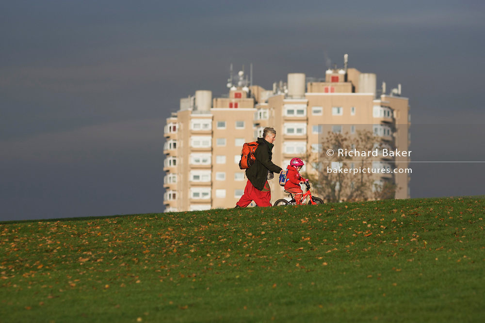 Local mother and child on bike with high-rise flats seen from Brockwell Park, Herne Hill, South London.