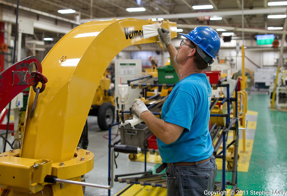 An employee peels off the protective paper on the lettering of a brush chipper on the assembly line in Plant 4 at Vermeer in Pella, Iowa on Thursday, July 28, 2011.