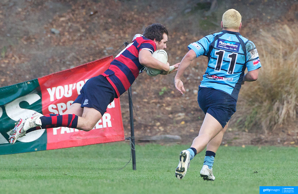 Rhys Chamberlain dives over fo score for Arrowtown watched by Mark Te Whaiti during the Wakatipu V Arrowtown Rugby Match at Queenstown Recreation Ground,  Queenstown, South Island, New Zealand, 11th June 2011