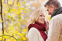 Portrait of Mature couple enjoying autumn while  showing affection in park
