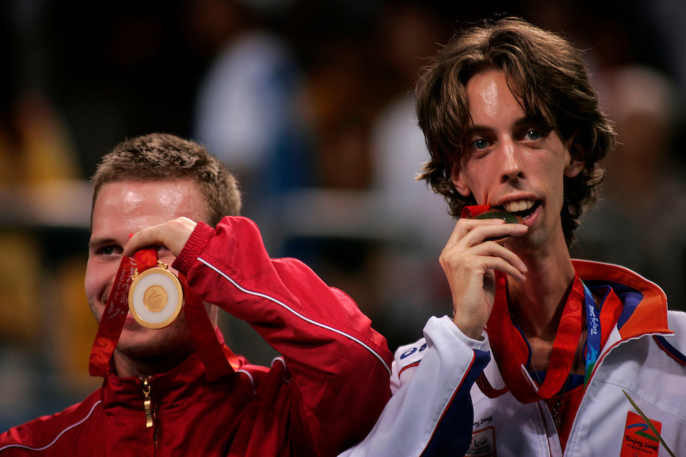 Denmark's Peter Rosenmeier, left, shows his gold medal as Netherland's Nico Blok bites his bronze medal, at the medal award ceremony for Singles Standing Class 6 Table Tennis at the Paralympic Games in against  Beijing , China, Thursday, Sept.11, 2008.