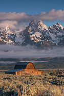 The spring sun breaks through the clouds and casts a golden glow on the John Moulton barn in Grand Teton National Park.