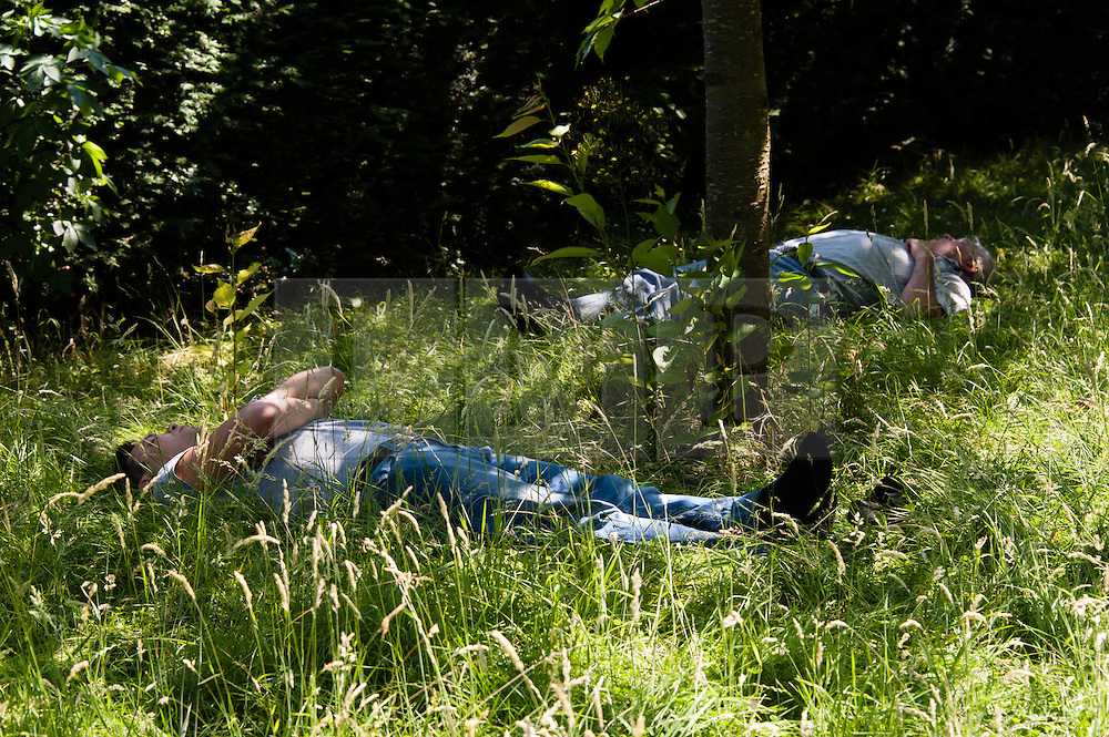 © Licensed to London News Pictures. 06/07/2013. London, UK.  Two men sleep in the shade provided by some trees in Regents Park, central london, during a sunny saturday.  Photo credit : Richard Isaac/LNP