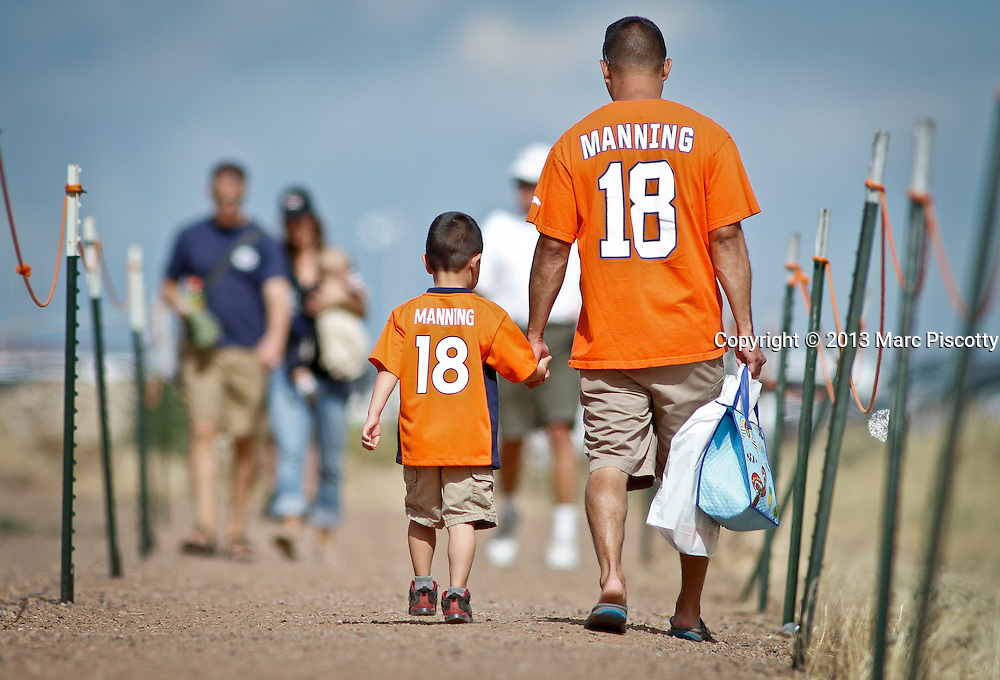 SHOT 8/1/13 9:57:50 AM - Denver Broncos and Peyton Manning fans walk out to their car after watching the team's training camp August 1, 2013 at Dove Valley in Englewood, Co.  (Photo by Marc Piscotty / © 2013)