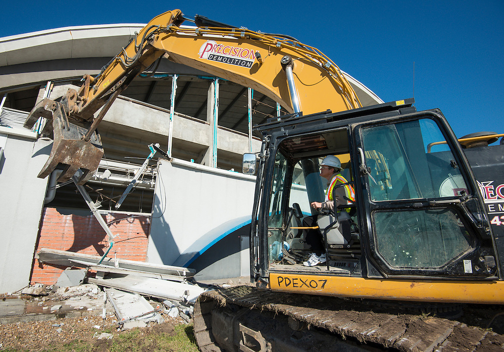 Houston ISD athletic director Marmion Dambrino operates a track hoe and helps with the demolition of the Delmar-Tusa Fieldhouse, January 16, 2014.