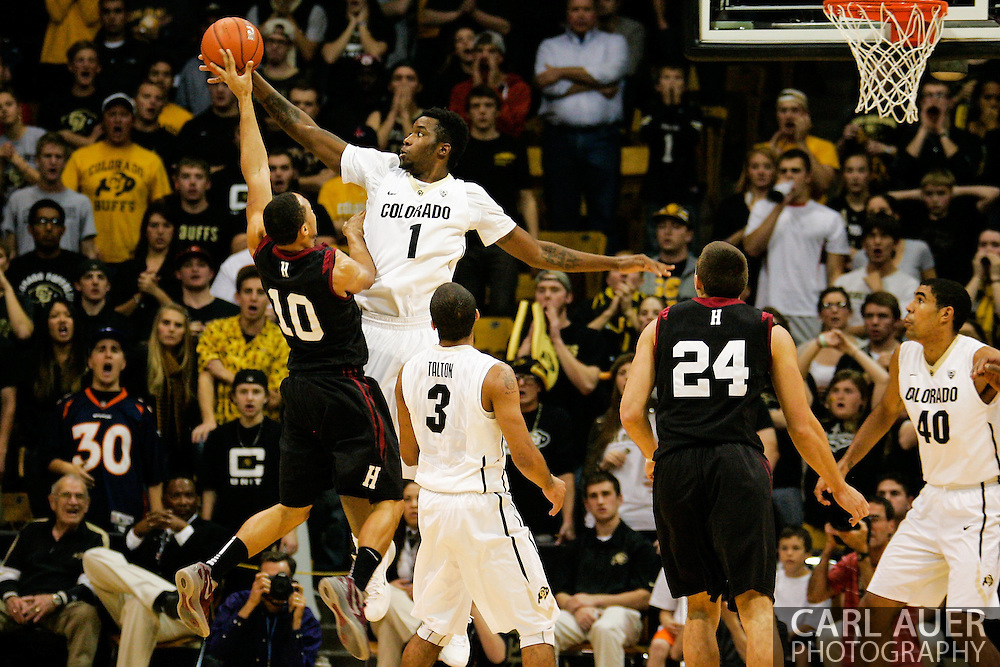 November 24th, 2013:  Colorado Buffaloes redshirt freshman forward Wesley Gordon (1) blocks a shot attempt by Harvard Crimson senior guard Brandyn Curry (10) in the second half of the NCAA Basketball game between the Harvard Crimson and the University of Colorado Buffaloes at the Coors Events Center in Boulder, Colorado