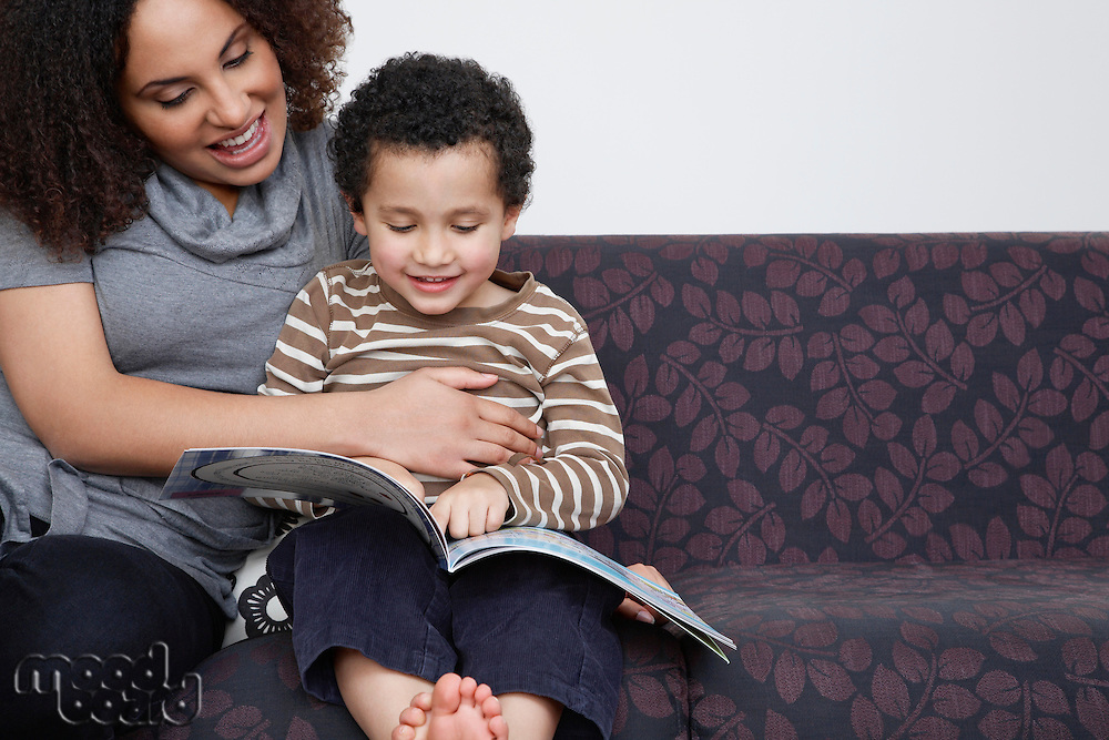 Mother reading book with son (5-6)
