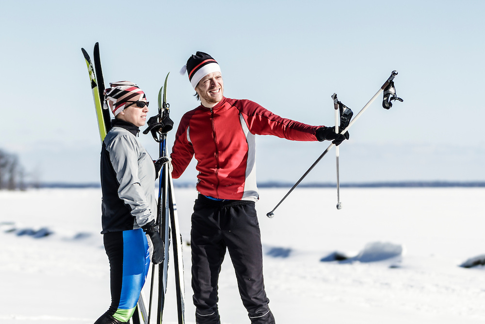 Happy male and female athletes getting ready for cross-country skiing.