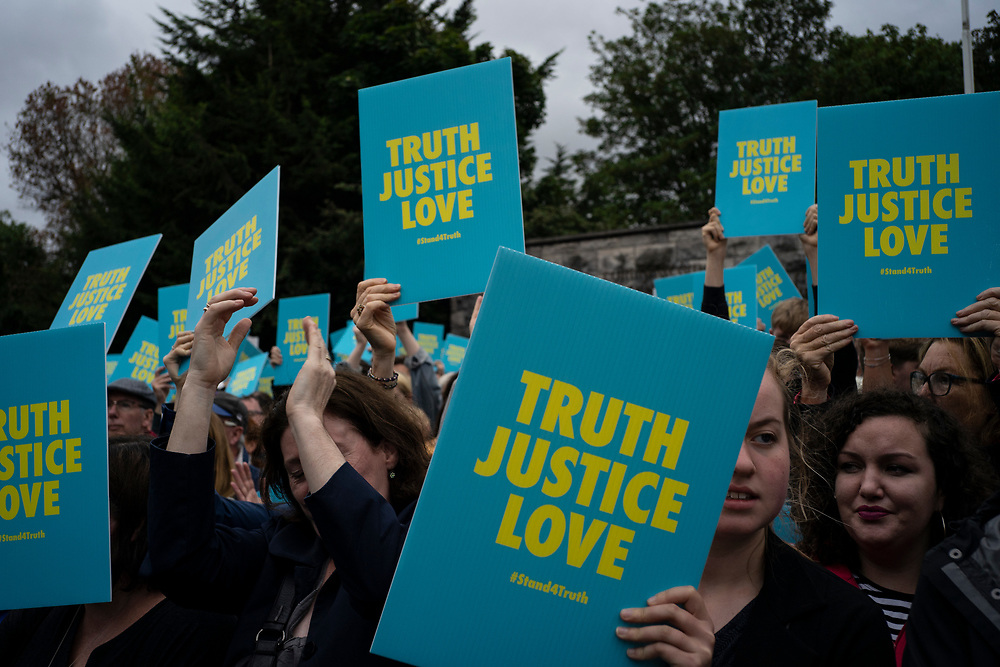 DUBLIN, IRELAND - AUGUST 26, 2018: People holding protest posters against clerical sexual child abuse in Ireland, during a protest gathering at the Garden of Remembrance in Dublin City centre. Thousands took the streets of Dublin protesting the wrongdoings of the Catholic Church, during the two day visit of Pope Francis to Ireland. CREDIT: Paulo Nunes dos Santos for The New York Times