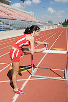 Female athlete stretching on hurdle