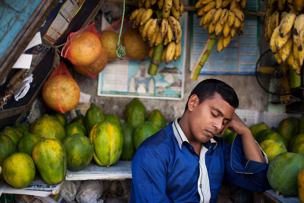 A local Bangladeshi man has a quick nap at his colorful fruit stall after a long morning working the Saturday market in Banderban in the Chittagong Hill Tracts of Bangladesh