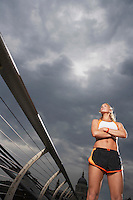 Female athlete standing on foot bridge low angle view