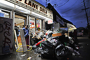 Dimple Shah, co-owner of the Sand Lane Deli with her husband Biyush Shah, hoses down shelves with their employee Omar Amin, following the destruction of Hurricane Sandy in the South Beach neighborhood of Staten Island, N.Y. on Nov. 2, 2012.