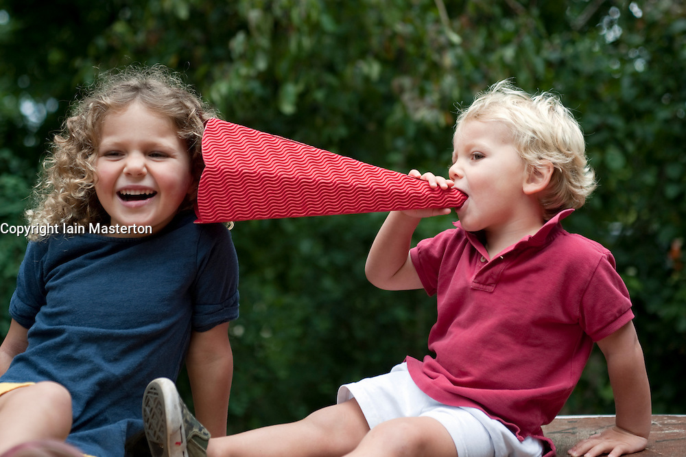 Young children using a toy cardboard megaphone to talk to each other while having fun