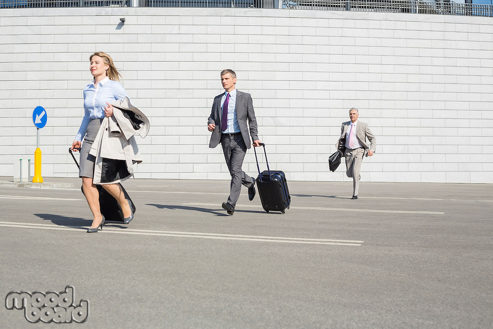 Businesspeople with luggage running on street