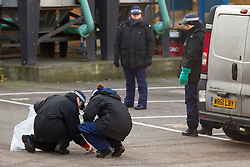 © Licensed to London News Pictures. 17/01/2013. London, UK. A police search team is seen examining the yard of a business located at the scene of yesterday's (17/01/13) helicopter crash in Vauxhall, London. 2 (two) people, including the pilot, died as a result of the incident and a further 11 (eleven) injured after the Augusta 109 helicopter collided with a tower crane in heavy mist showering wreckage onto cars below. Photo credit: Matt Cetti-Roberts/LNP