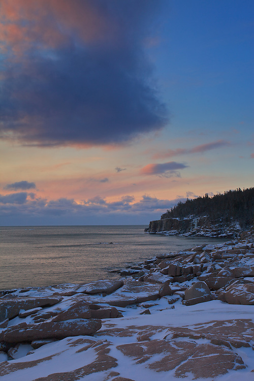Visitors to Acadia National Park in the winter will be rewarded with vistas of snow-accented pink granite shorelines and the quiet beauty of frozen lakes without the crush of the  summer crowd. Here, Otter Rocks catches the first rays of the sun on a cold morning in February.