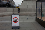 Children ignore a no climbing safety sign, to haul themselves on to the plinth of Nelson's Column, on 15th December 2016, in Trafalgar Square, London, England.