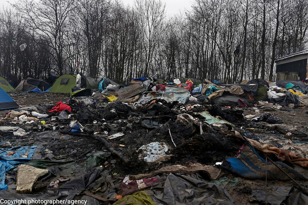 Abandoned and burnt-out tents litter a muddy field in Grande Synthe nera Dunkirk in northern France. Some 2500 refugees hoping to make the crossing to the UK are living in deplorable conditions in this de facto refugee camp.