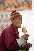 Buddhist spinning a hand held prayer wheel, Bhutan