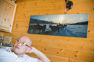 Permafrost scientist Kenji Yoshikawa in his cabin outside Fairbanks. A photograph of one of his travels with reindeers in Siberia is displayed on the wall.