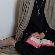 Hermit Sister Rachel Denton sits with a bible in her prayer room in St Cuthberts' Hermitage in Lincolnshire, north east Britain April 27, 2015. Sister Rachel Denton has vowed to spend the rest of her life living as a consecrated hermit in the Catholic faith. A hermit is a person who chooses to live alone, with the intention of finding God. Rarely leaving her house she lives a life of prayer and solitude. However, she uses the internet and social media to share her experience and distance her self from physically interacting with society. REUTERS/Neil Hall