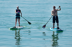 © Licensed to London News Pictures. 05/05/2018. Worthing, UK. Paddle boarders enjoy the sunshine in sea off Worthing Pier. Record temperatures are expected this bank holiday weekend. Photo credit: Peter Macdiarmid/LNP