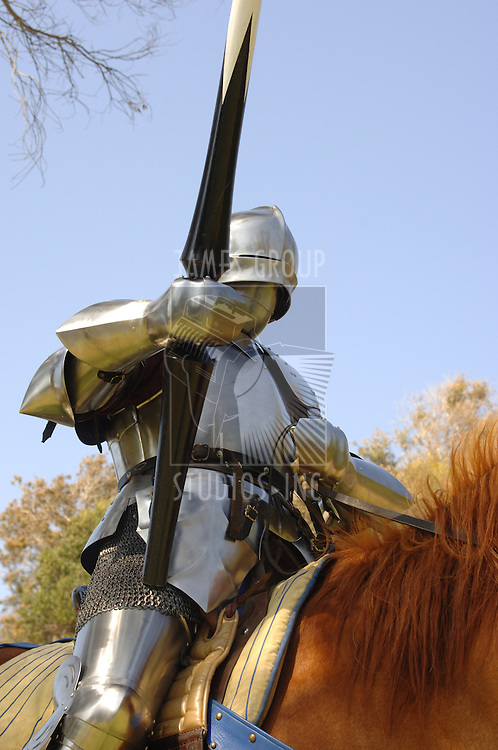 Medium shot of a 15th century English knight in full armour holding a lance on horseback