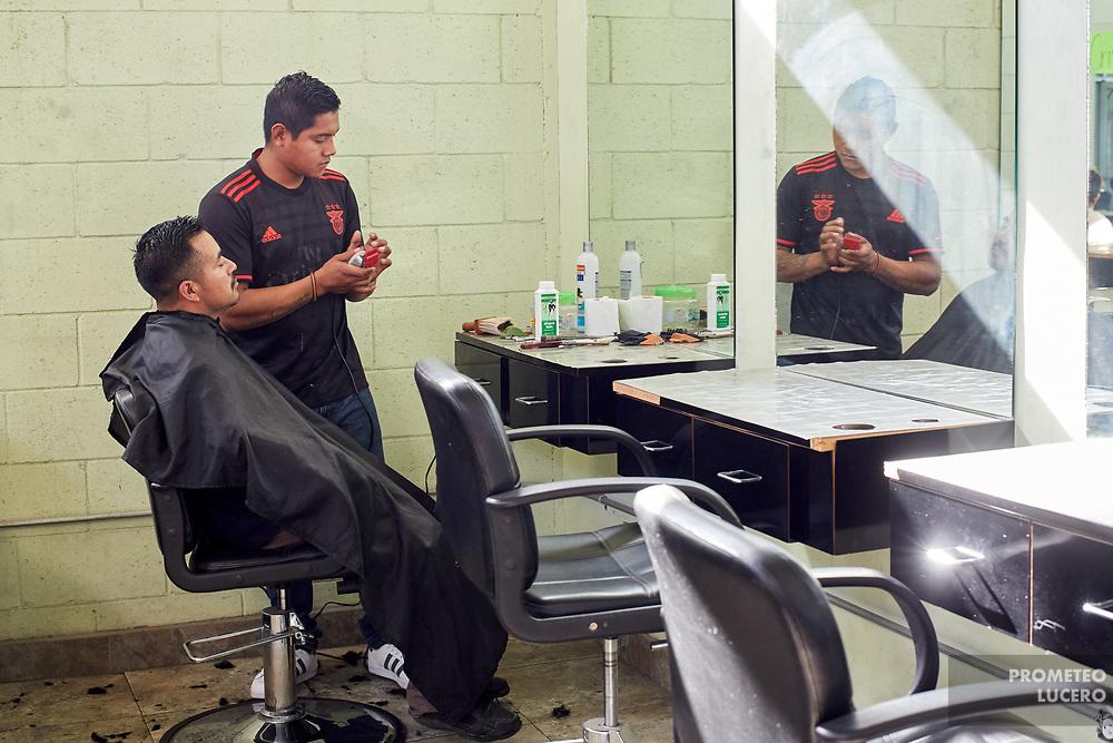 A barber shaves the beard of a deported person who wants to seek employment. For the personnel of the Desayunador Salesiano, it is important for people to preserve their dignity, even after being deported. // Un barbero afeita el rostro de una persona deportada que busca empleo. Para el personal del Desayunador Salesiano, es importante que las personas conserven su dignidad aún después de ser deportados. (Prometeo Lucero)