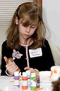Kaitlin Krumnauer, who attends Waynesville Elementary use craft supplies to add a personal touch to a candle at the American Girl Tea Party, Saturday, January 27, 2007 in Waynesville's Mary L. Cook Library.