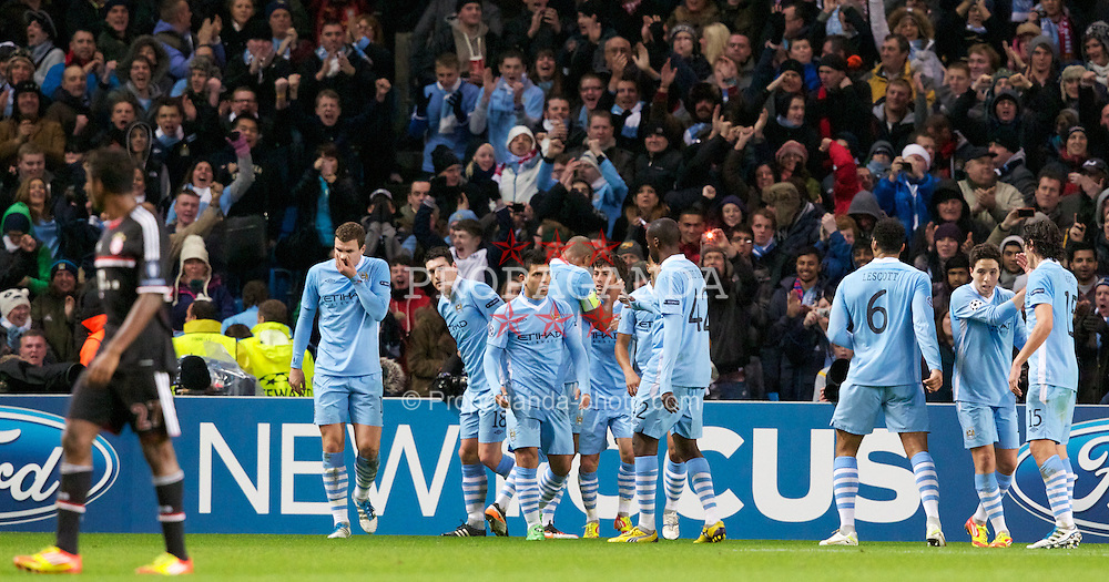 MANCHESTER, ENGLAND - Wednesday, December 7, 2011: Manchester City's David Silva celebrates scoring the first goal against FC Bayern Munchen with team-mate and captain Vincent Kompany during the UEFA Champions League Group A match at the City of Manchester Stadium. (Pic by Vegard Grott/Propaganda)