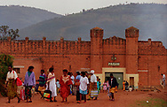 The friends and family of some of the 6,152 men, women and children being held within the walls of Kigali prison walk away after making a visit.  The prison is packed with those people accused of taking part in last year's ethnic massacres in wich nearly 1 million Rwandans lost their lives. The new government has been unable to rebuild the justice system so the inmates have not been charged or tried in a court. Berkins (1 of 7)