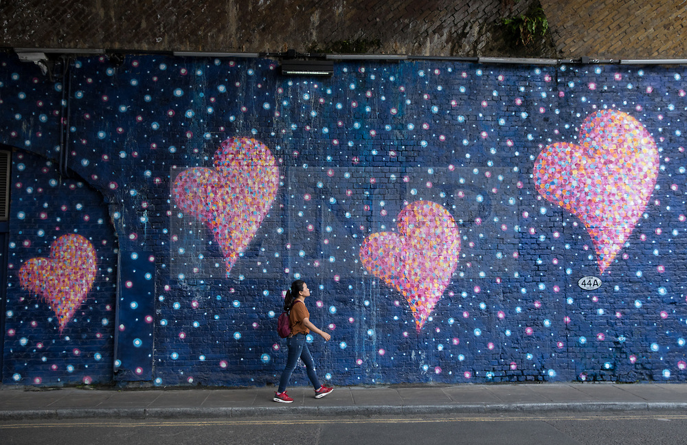 © Licensed to London News Pictures. 03/06/2018. London, UK. A woman walks past a heart mural near Borough Market, on the anniversary of the London Bridge and Borough Market terror attack. A series of events are taking place throughout the day, including a service of commemoration at Southwark Cathedral, the planting of an olive tree in the Cathedral grounds, a minute's silence at 4:30pm and the laying of flowers.  Photo credit : Tom Nicholson/LNP