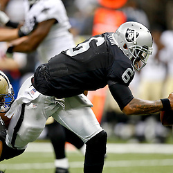 Aug 16, 2013; New Orleans, LA, USA; New Orleans Saints defensive end Glenn Foster (74) sacks Oakland Raiders quarterback Terrelle Pryor (6) during the second half of a preseason game at the Mercedes-Benz Superdome. The Saints defeated the Raiders 28-20. Mandatory Credit: Derick E. Hingle-USA TODAY Sports