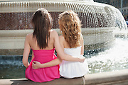 Back view of two young female friends with arms around sitting by water fountain